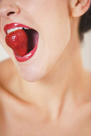 bathtowel: Close up studio shot of Hispanic woman with strawberry in mouth LANG_EVOIMAGES