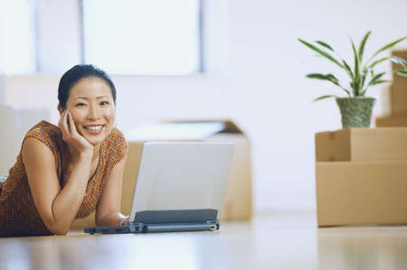 south western european descent: Asian woman using laptop in new house with boxes