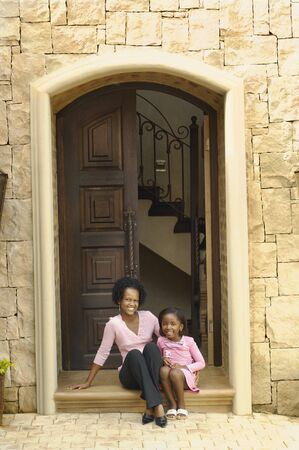 solicitous: African mother and daughter sitting on doorstep LANG_EVOIMAGES