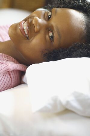 casualness: Close up of young African woman laying down and smiling
