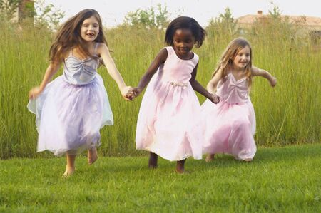 solicitous: Young girls wearing party dresses and running in field