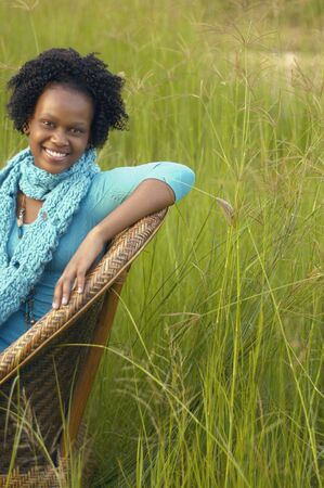 stepping: Young African woman sitting in chair in field