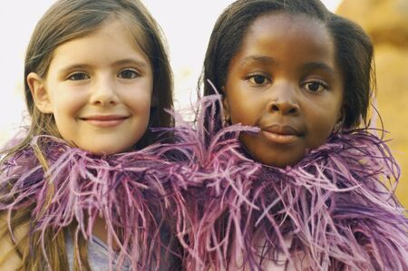 feather boa: Two young girls wearing feather boa and smiling LANG_EVOIMAGES