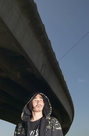 disgruntled: Young Asian man standing under raised highway LANG_EVOIMAGES