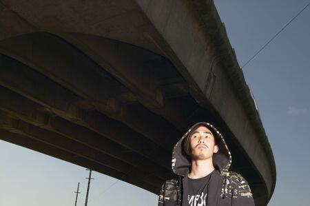 Young Asian man standing under raised highway Stock Photo