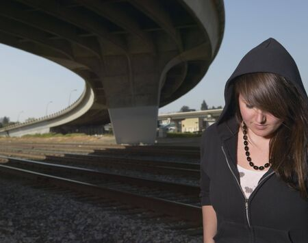 Young woman standing under raised highway