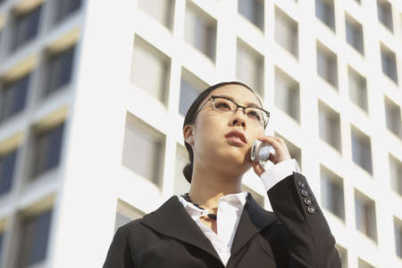 low  angle: Low angle view of Asian businesswoman using cell phone