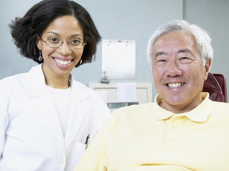 African female dentist with senior male patient 스톡 콘텐츠