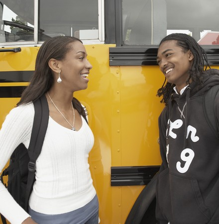 Young African couple leaning against school bus talking Reklamní fotografie