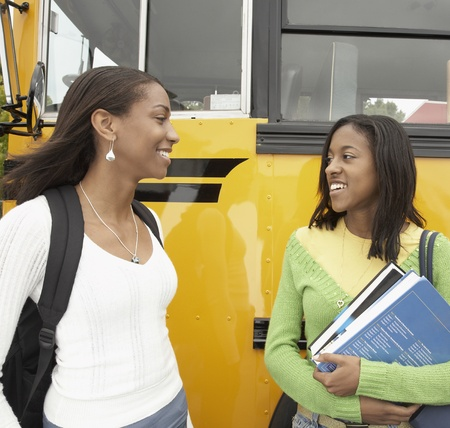 motorcoach: Two young African women next to school bus talking