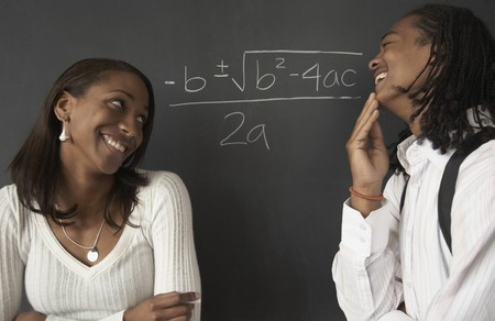 Two African students next to math problem on blackboard 스톡 콘텐츠