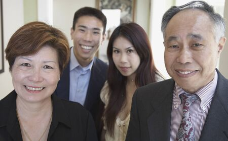 Asian family smiling indoors Stock Photo