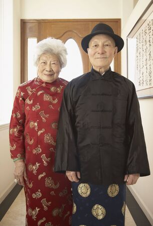 Senior Asian couple in traditional dress indoors