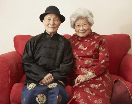 ソファの上の伝統的なドレスの上級アジア カップル