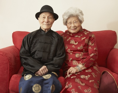 Senior Asian couple in traditional dress on sofa