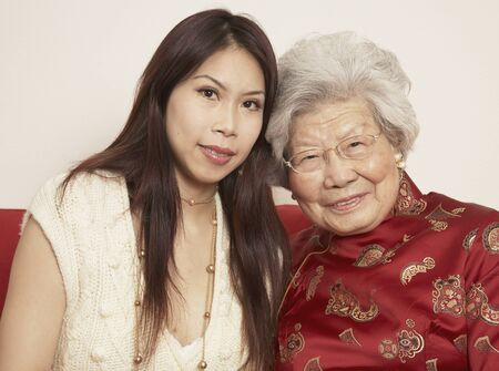 ninetys: Asian grandmother with adult granddaughter smiling