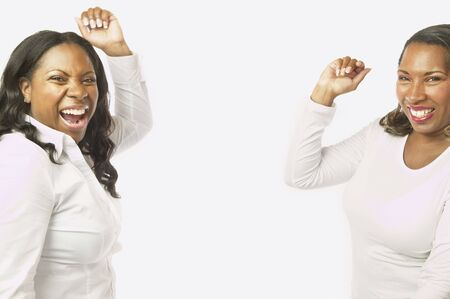 Adult African sisters laughing and dancing Stock Photo