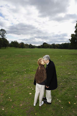 solicitous: Senior couple kissing in open meadow LANG_EVOIMAGES