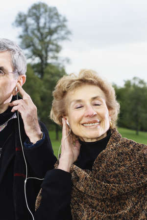 longshot: Senior couple listening to same mp3 player outdoors LANG_EVOIMAGES