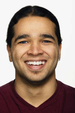 devilment: Close up studio shot of Hispanic man smiling
