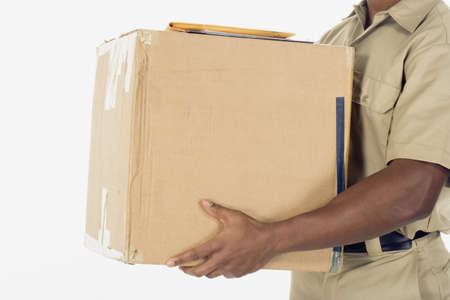 facing away: Studio shot of African delivery man with package
