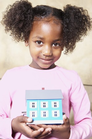 davenport: Young African girl holding tiny house