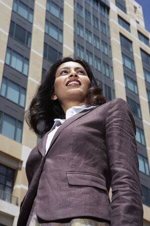 north western european descent: Low angle view of Indian businesswoman in urban scene LANG_EVOIMAGES
