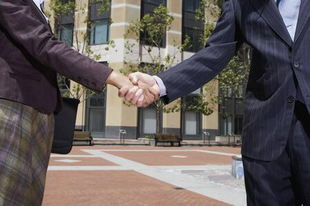 fulfilling: Businesswoman and businessman shaking hands outdoors