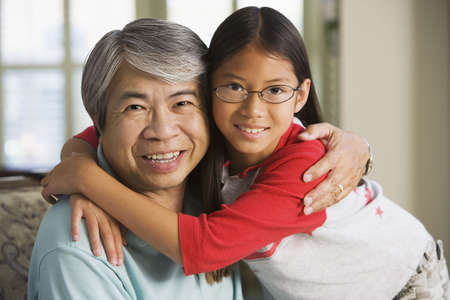 solicitous: Asian grandfather hugging granddaughter indoors