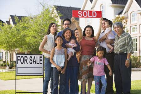 familias unidas: Multi-generacional familia asiática sosteniendo signo Vendido en frente de la casa