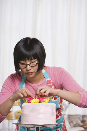 facing away: Young Asian woman putting flowers on cake