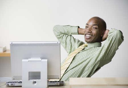 African businessman sitting at desk smiling