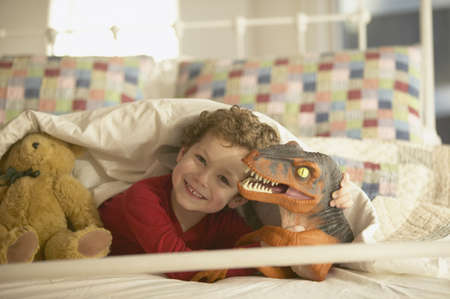ninety's: Young boy smiling in bed with toy dinosaur