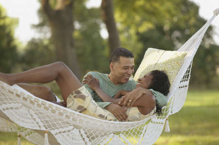 dating: Middle-aged African couple hugging in hammock
