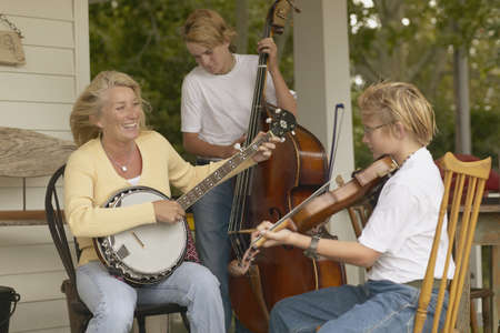 ninetys: Mother and sons playing instruments together on porch