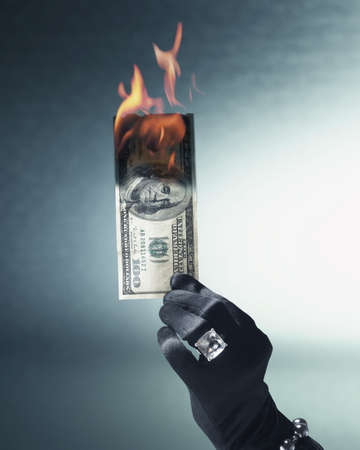 jeweled: Womans gloved and jeweled hand holding burning US hundred dollar bill