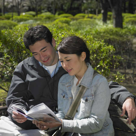 wooing: Asian couple looking at guide book in park