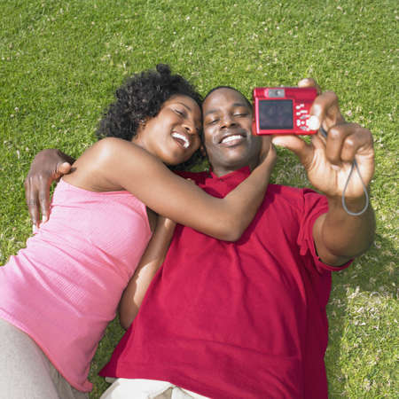 mischievious: African couple laying on grass and taking own photograph