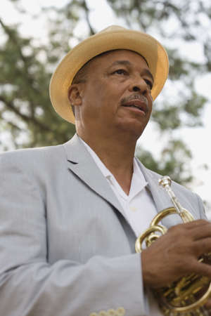 wearying: Senior African man holding trumpet LANG_EVOIMAGES