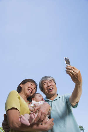 generation gap: Asian grandparents holding baby grandchild and taking photograph