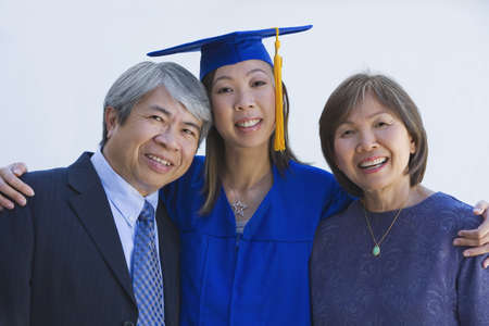 gramma: Asian woman in graduation cap and gown with parents