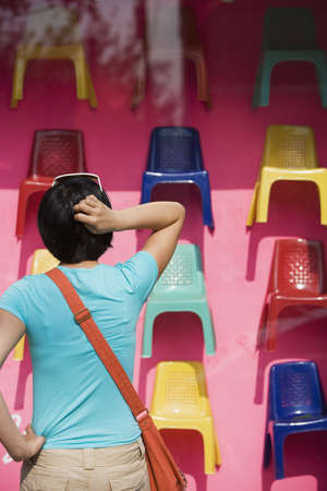 south asian ethnicity: Woman looking at plastic chairs in store window
