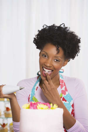 decorating: Young African woman decorating cake