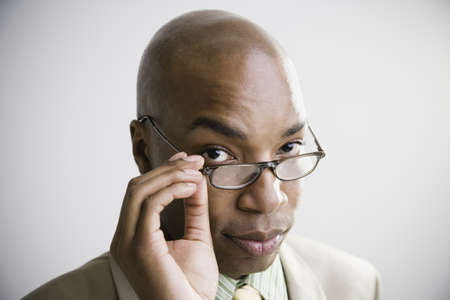 motioning: African businessman with hand on eyeglasses
