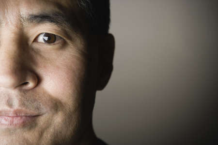 mid life: Close up of half of Asian mans face LANG_EVOIMAGES