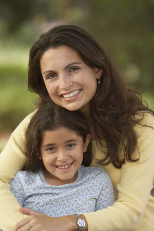 ninetys: Hispanic mother and daughter hugging and smiling