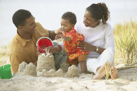 dressup: African parents and toddler building sand castle at beach LANG_EVOIMAGES