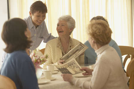 senior friends: Senior woman talking and laughing with friends LANG_EVOIMAGES
