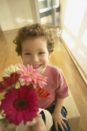 bedcover: Young boy smiling and offering flowers