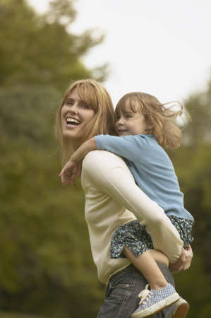 entertainers: Mother giving young daughter piggyback ride outdoors